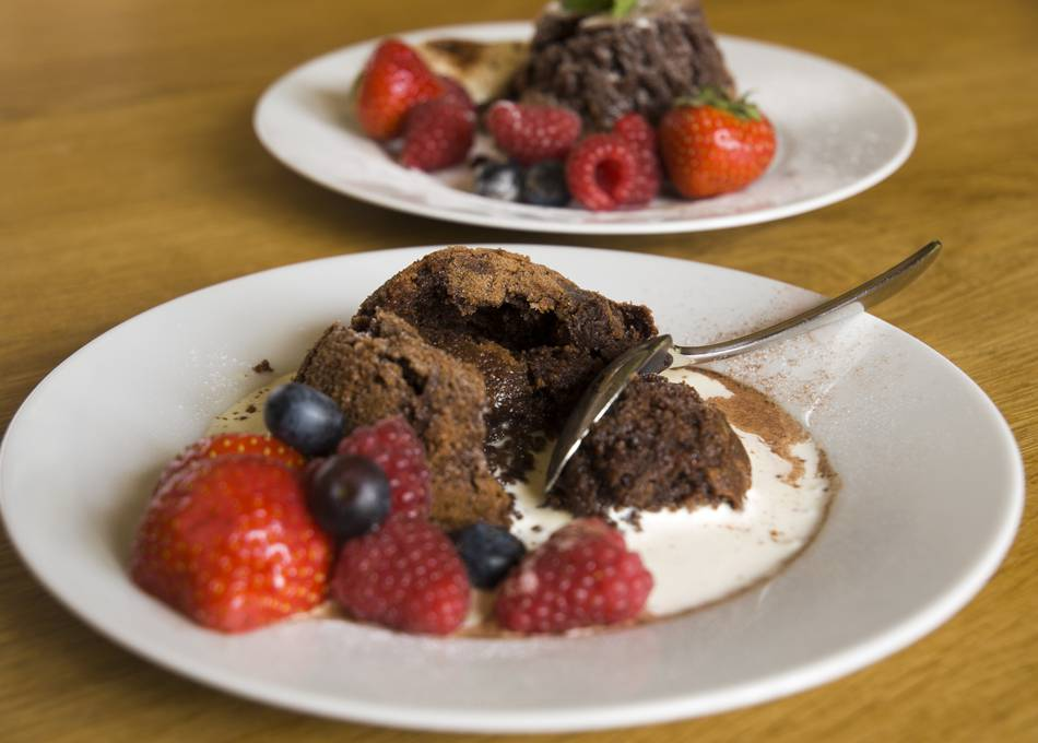 Hot chocolate puddings with berries and cream